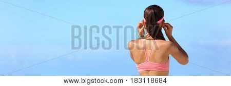 Fitness woman putting on earphones getting ready for morning run listening to music with headphones wearing wearable tech accessories banner copyspace on blue sky background. poster
