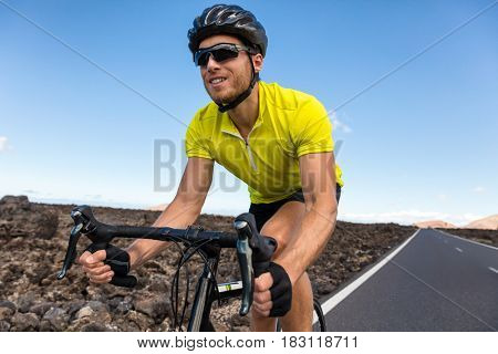 Cyclist man biking riding road bike training for triathlon. Biker on cardio workout on open road. Professional sports athlete living an active and healthy lifestyle.