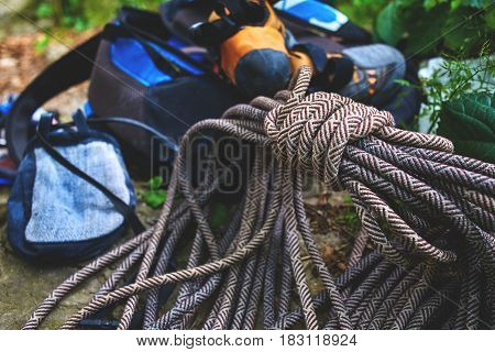 climbing equipment on the ground. climbing rope, climbing shoes, chalk bag and backpack