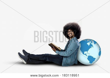 Afro student sitting with globe while holding a book and smiling at the camera isolated on white background