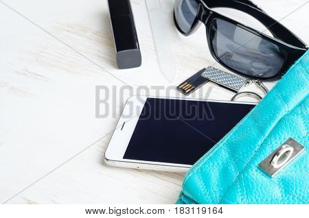 Woman's bag and it's content - phone, lipstick, sunglasses, nail file, USB flash drive