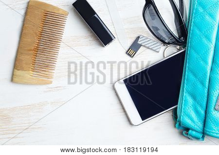 Woman's bag and it's content - phone, lipstick, sunglasses, nail file, USB flash drive, comb