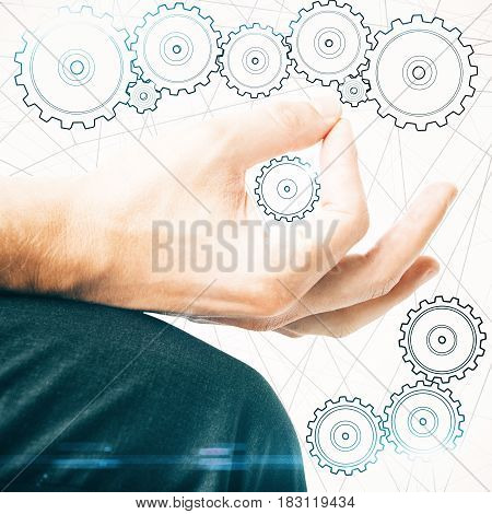 Creative image of male hand drawing abstract drawn cogwheels. Teamwork concept