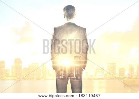 Back view of young businessman on abstract city background with sunlight and business chart arrow. Financial growth concept. Double exposure