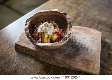 Wooden bowl on the same board on the tabletop. There is a mix of exotic fruit with seeds and nuts in the bowl. Closeup. Horizontal.