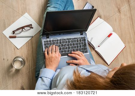 Top View Of Woman With Laptop Is Sitting On Floor
