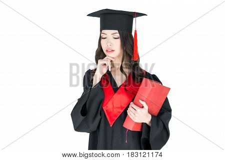 Thoughtful Young Brunette Woman In Mortarboard Holding Book On White