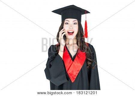 Surprised Young Brunette Woman In Mortarboard And Academic Gown Looking At Camera