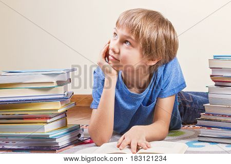 Smiling kid between the stacks of books. Education, back to school concept