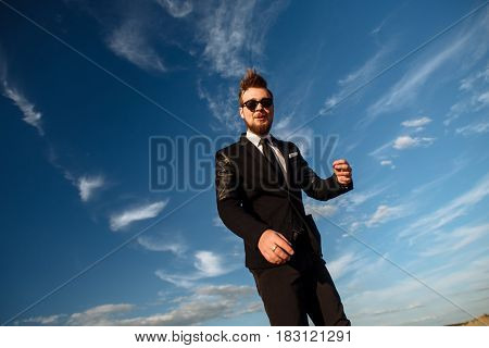 Beautiful Young Man With Smile In Suit Wear And Sunglasses Standing Barefoot In Desert Enjoying Natu