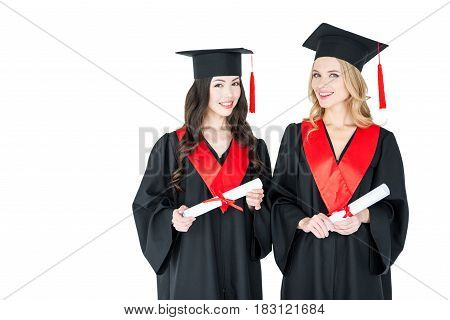 Two Happy Young Women In Academic Gowns And Mortarboards Holding Diplomas