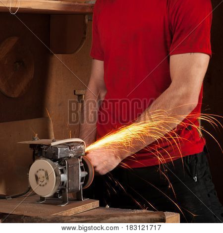 A man working on a grinding machine without safety equipment, sparks fly, red shirt,