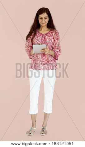 Indian woman standing and using tablet