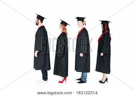 Full Length Side View Of Students In Academic Caps And Graduation Gowns Standing In A Row