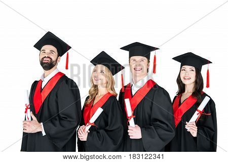 Happy Students In Graduation Gowns And Mortarboards Holding Diplomas On White