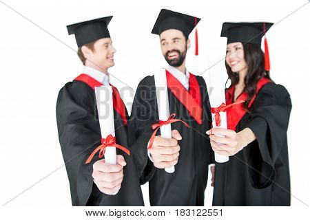 Happy Students In Graduation Caps Holding Diplomas And Smiling Each Other