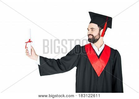 Happy Young Man In Graduation Gown Holding Diploma