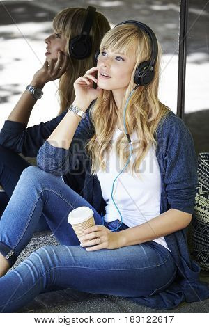 Young blond woman relaxing with headphones in city