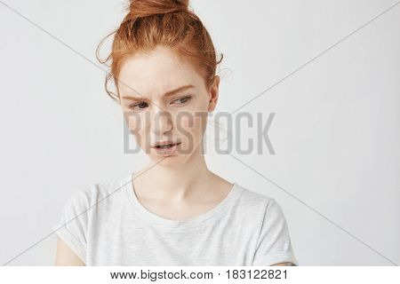 Portrait of young beautiful dissatisfied redhead girl with freckles. Copy space. Isolated on white background.