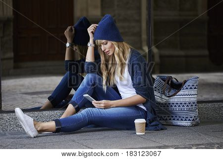 Beautiful young woman texting in city sitting on ground