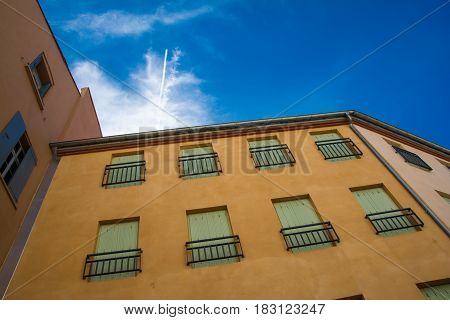 underneath view of traditional colorful buildings in downtown Perpignan