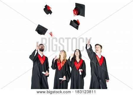 Happy Young Students With Diplomas Throwing Graduation Caps Isolated On White