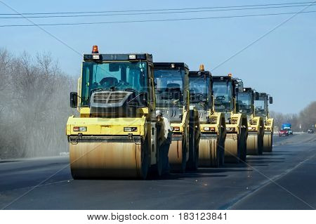 Several yellow asphalt road rollers on road