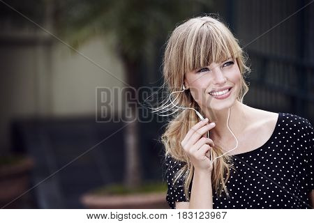 Young woman smiling as she communicates with earphones and mic