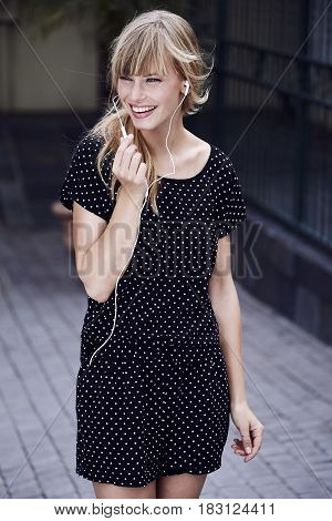 Beautiful woman in spotted dress with earphones