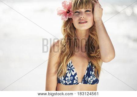 Blue eyed bikini babe wearing flower in hair portrait