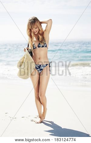 Bikini babe walking on beach smiling looking down