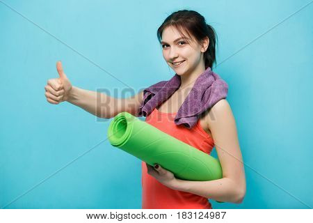 Happy woman holds fitness mat in gym