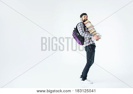 Full Length Of Bearded Student With Pile Of Books On White With Copy Space