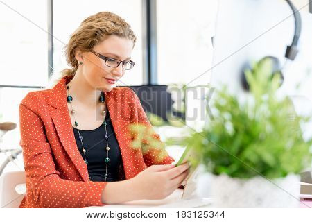 Young woman in office holding a photo frame