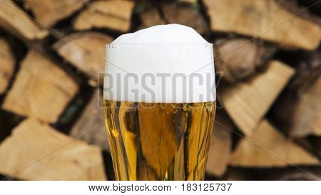 closeup of glass of beer with froth in front of firewood