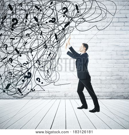 Side view of young businessman pushing abstract scribble and question marks on white brick background. Confusion concept