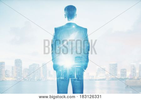Back view of young businessperson on abstract city background with daylight and business chart arrow. Income concept. Double exposure