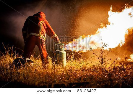 firefighters try to control fire burning with high pressure water