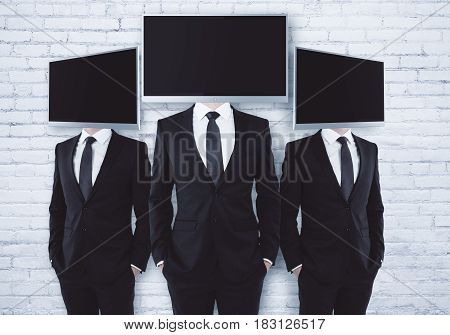 Three screen headed businesspeople on brick background. Mock up