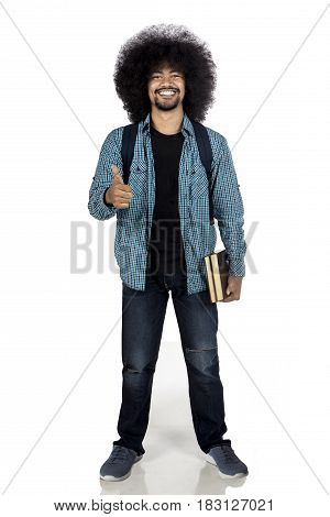 College student showing thumb up while holding a book and standing in studio isolated on white background