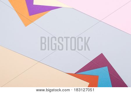 Color papers geometry flat composition background with violet blue orange and grey tones.