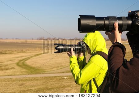 Two paparazzi with long lens in the nature
