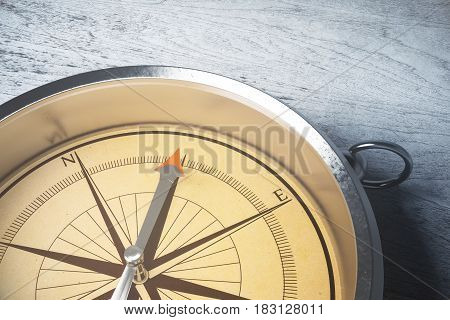 Close up of amber compass on light surface. Orienteering concept. 3D Rendering