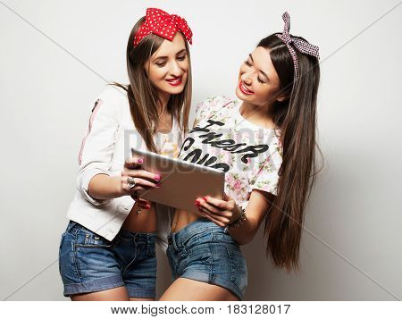 lifestyle, tehnology and people concept: Happy girls  with tablet computer over white  background.