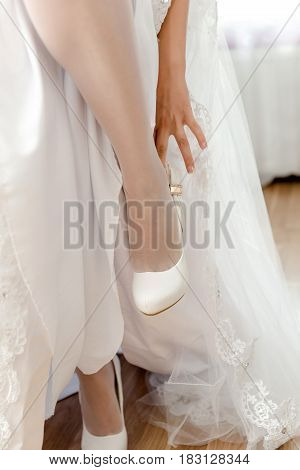 The bride standing on one leg and the second leg pulled a white shoe.