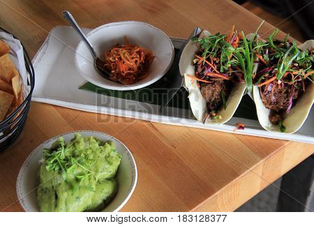 Pulled pork tacos and dressing set on wood table of local restaurant.