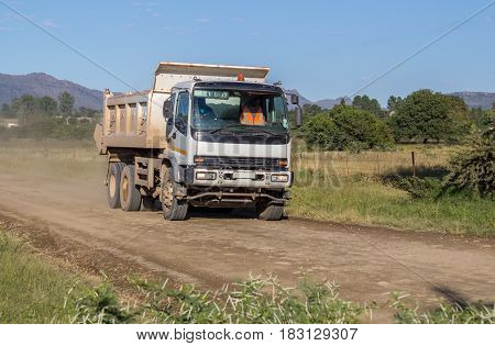 White construction truck moving fast with load of rock and sand on rural dirt road - photograph