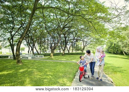 Image of cute boy learns to ride a bike with his family while walking together in the park
