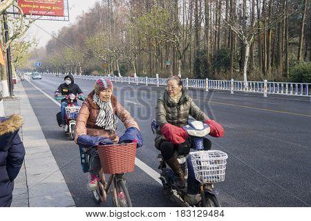 HANGZHOU China. April 18 2017: Elderly chinese women rides bicycle on the West Lake street in Hangzhou China