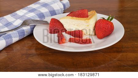 A slice of fresh cheesecake topped with strawberries